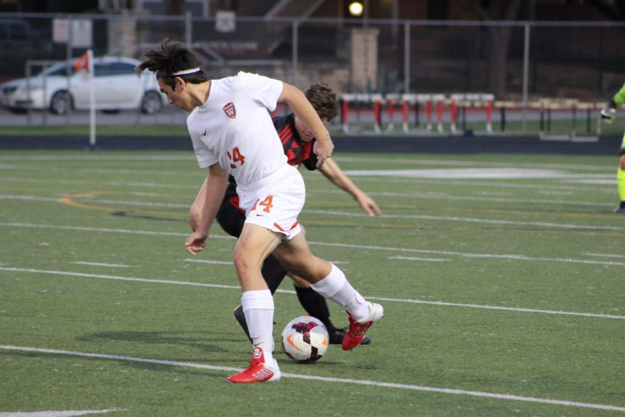 Felipe Centeno '19 attempts to get the ball away from opposing team member.