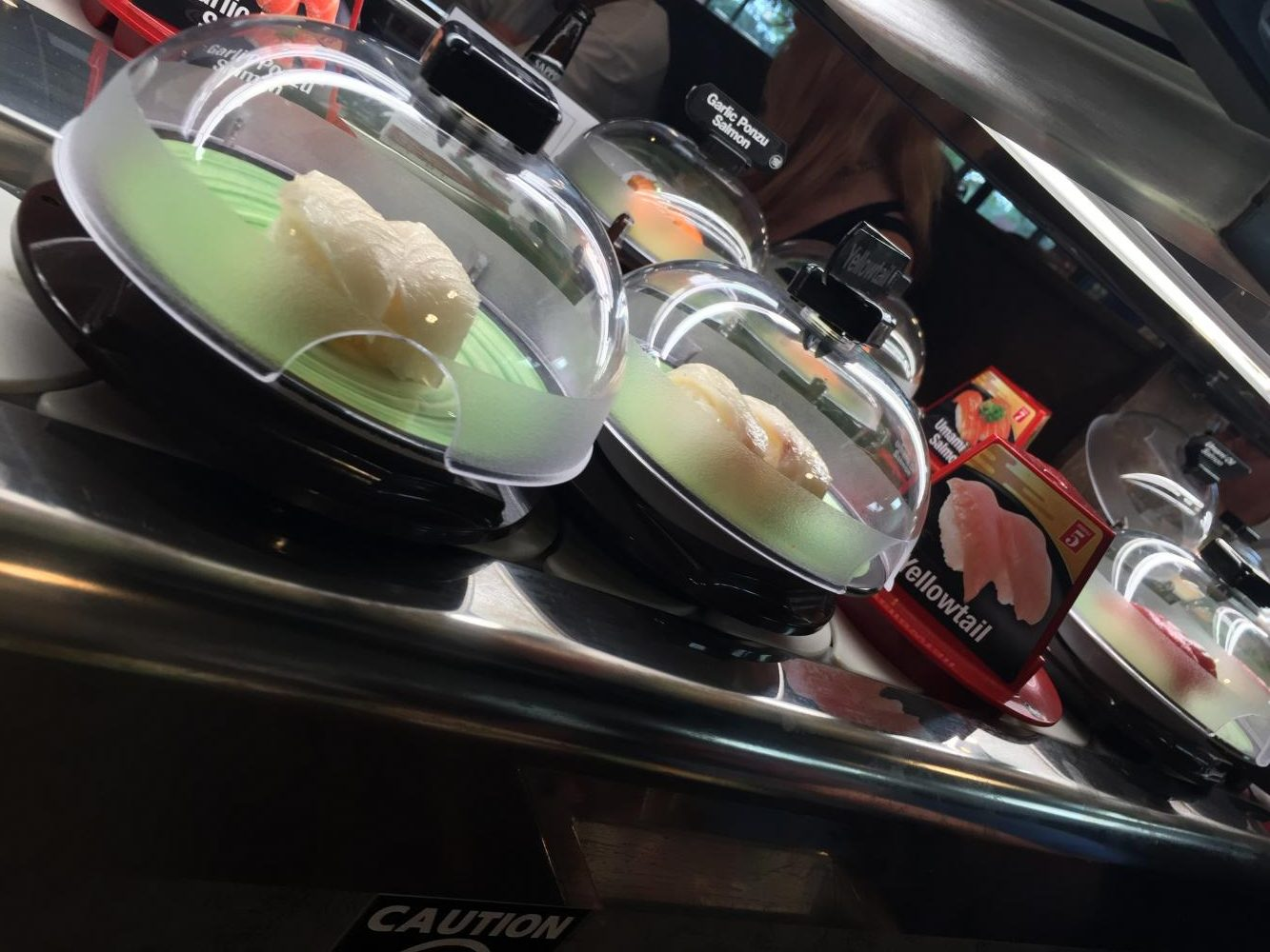 Different types of sushi travel by the table in dome containers to maintain freshness.
