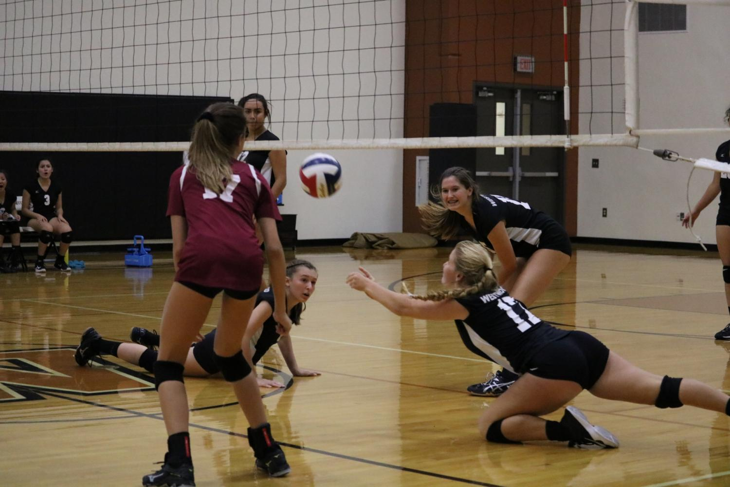 Freshmen+Lauren+Tyndall+and+Colleen+Wyrick+dig+for+the+ball.