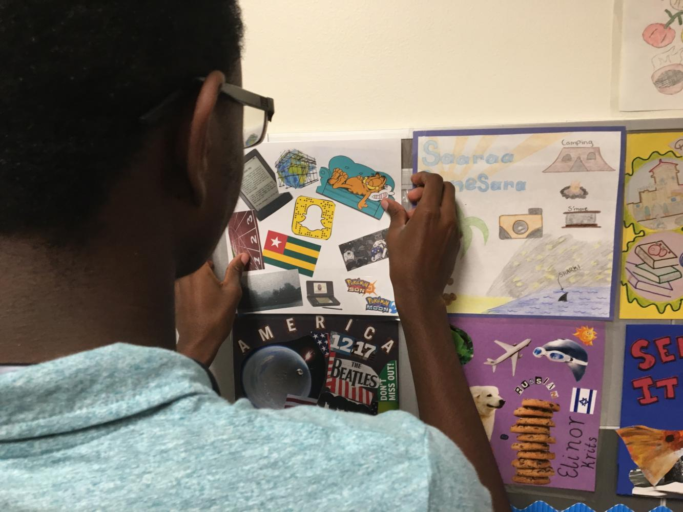 Karim Cisse '19 hangs his quilt square on the wall next to many others.