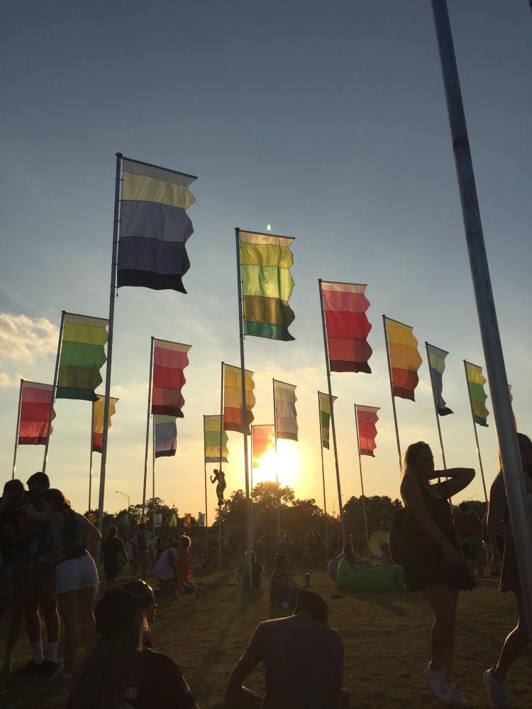 The+sunset+on+Sunday+peers+through+the+flags+at+the+top+of+the+hill.