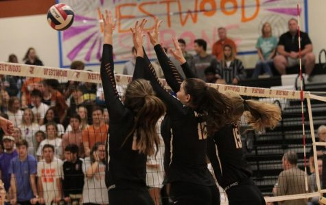 Maddi Kriz '19, Emily Low '18, and Cassie Jackson '18, jump together to block the other teams hit.
