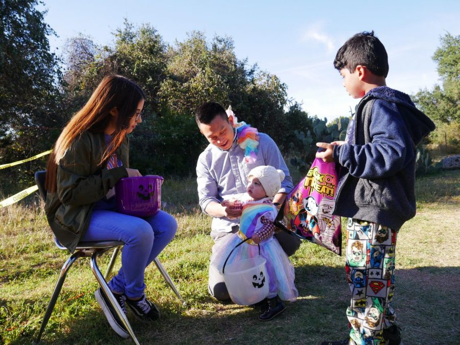 Fernanda Roa Campos '19 passes out candy to the trick-or-treaters walking along the trail.