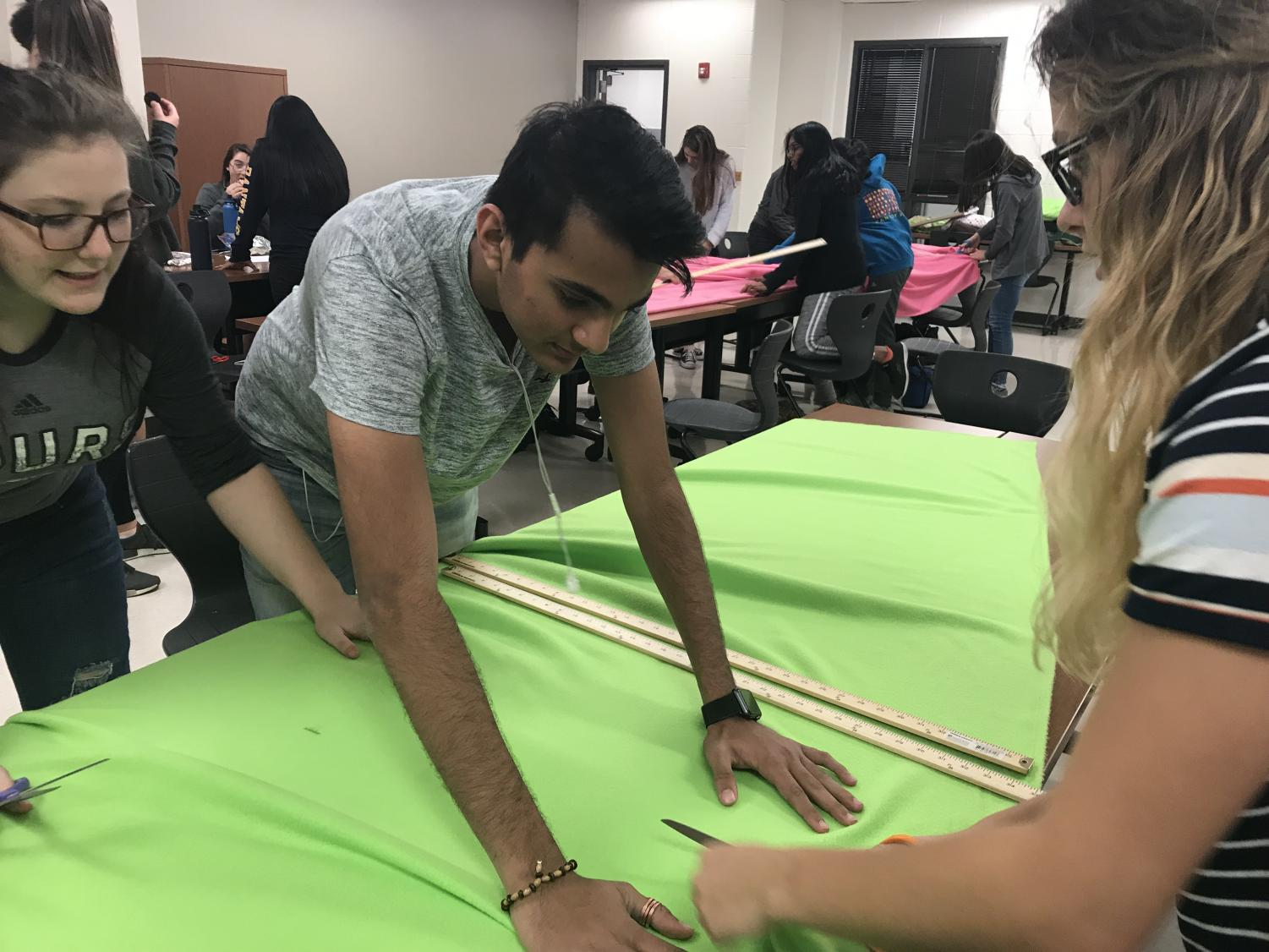 Isabel Cameron '19 and Azaan Moledina '19 help Mikayla Piwonka '19 cut the fabric. Photo courtesy of UNICEF Club.