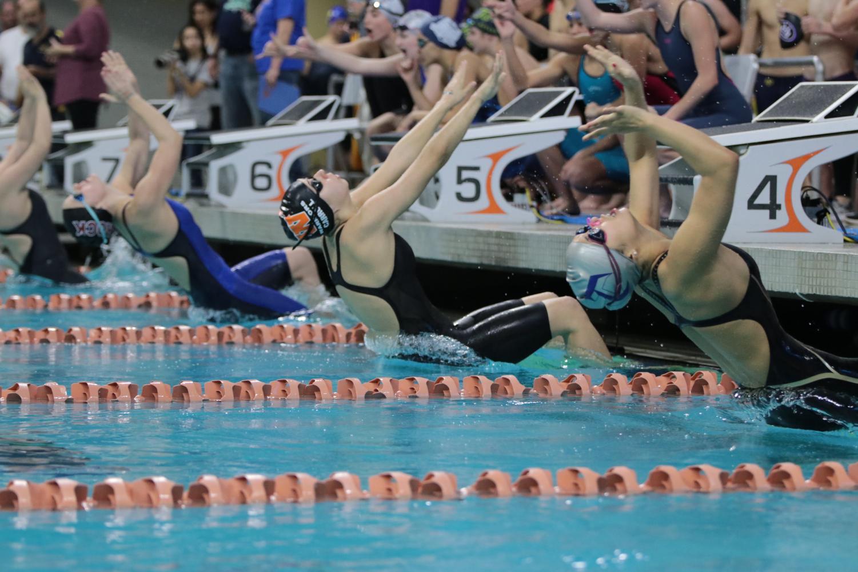 Ashlyn+Carroll+%2718+pushes+off+the+wall+to+start+her+backstroke+race.