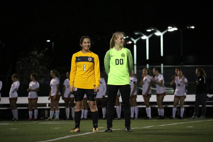 Bella Garcia 21 and Madison Broadbent 21 wait for their teammates to shake their hands.