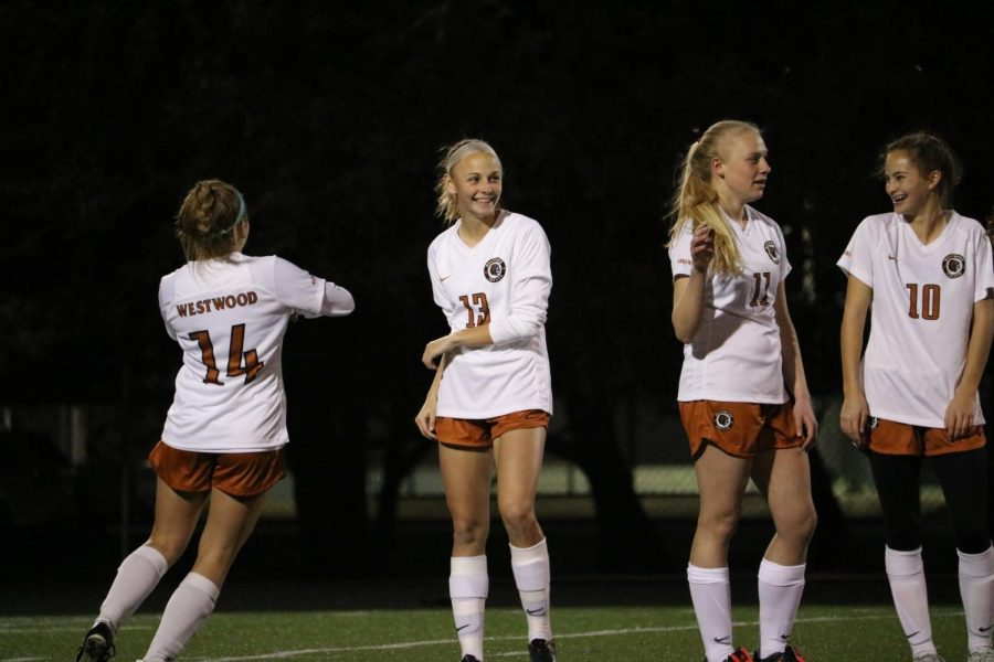 The varsity girls shake high five each other before game.