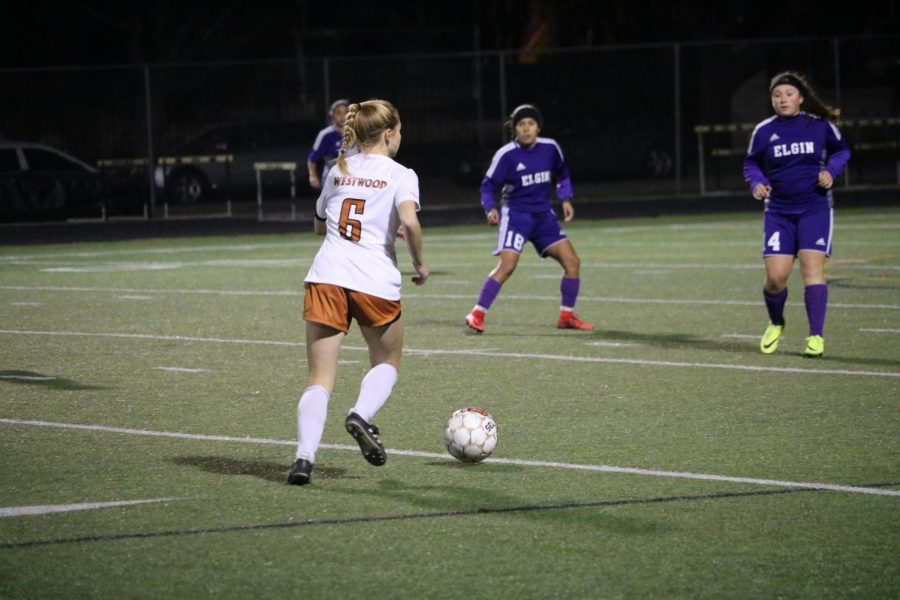 Ella Concannon 18 dribbles the ball down field.