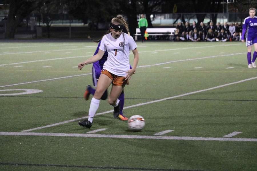 Claire Tinker 19 dribbles away from opposing player.