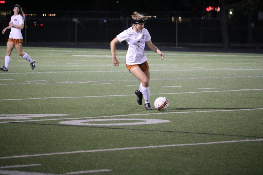 Claire Tinker 19 dribbles down field to pass to a teammate.