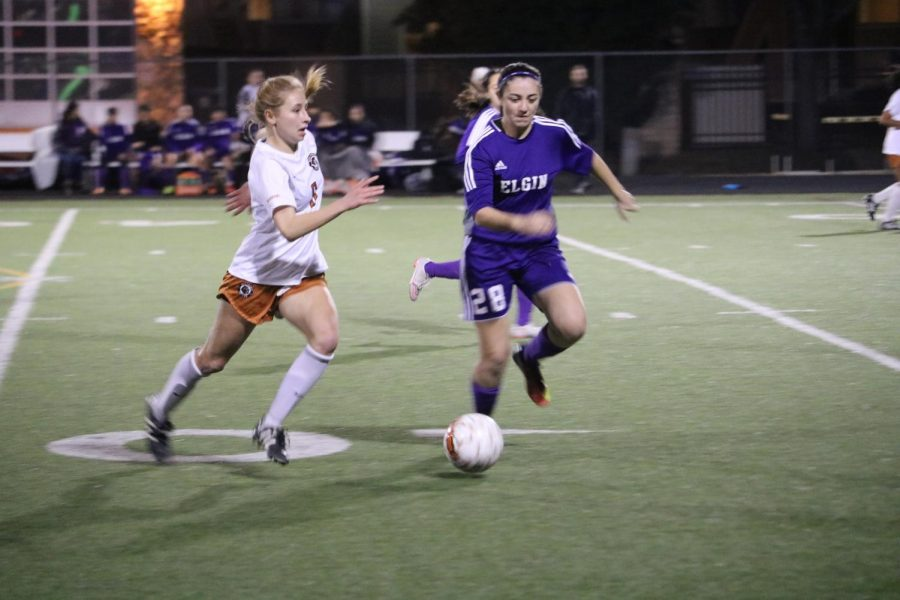 Ella Concannon 18 attempts to dribble away from opposing player.