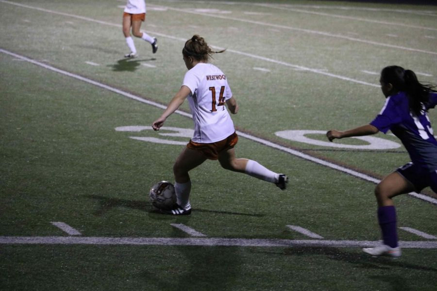 Christina Stephenson 18 prepares to kick ball to teammate.