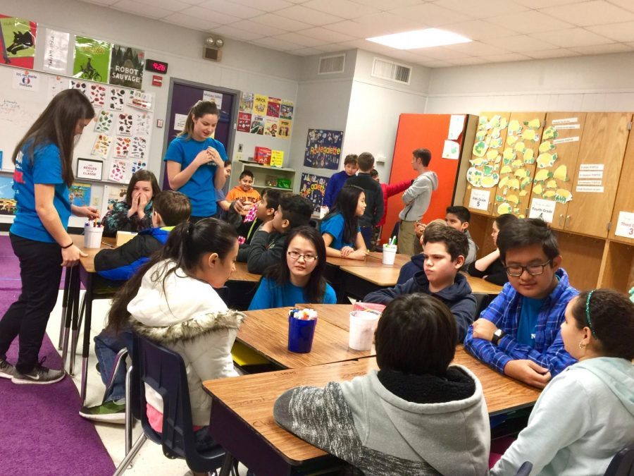 IB students sit with groups of elementary students to teach them French. Photo Credit to Ms. Anne Macharia.