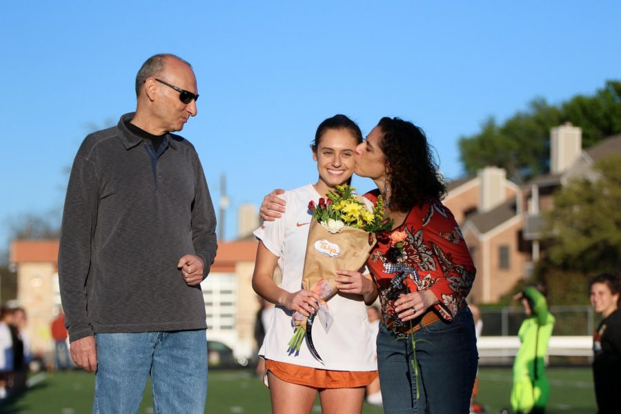 Talya Shalev's '18 mom kisses her on the cheek while being recognized at senior night.