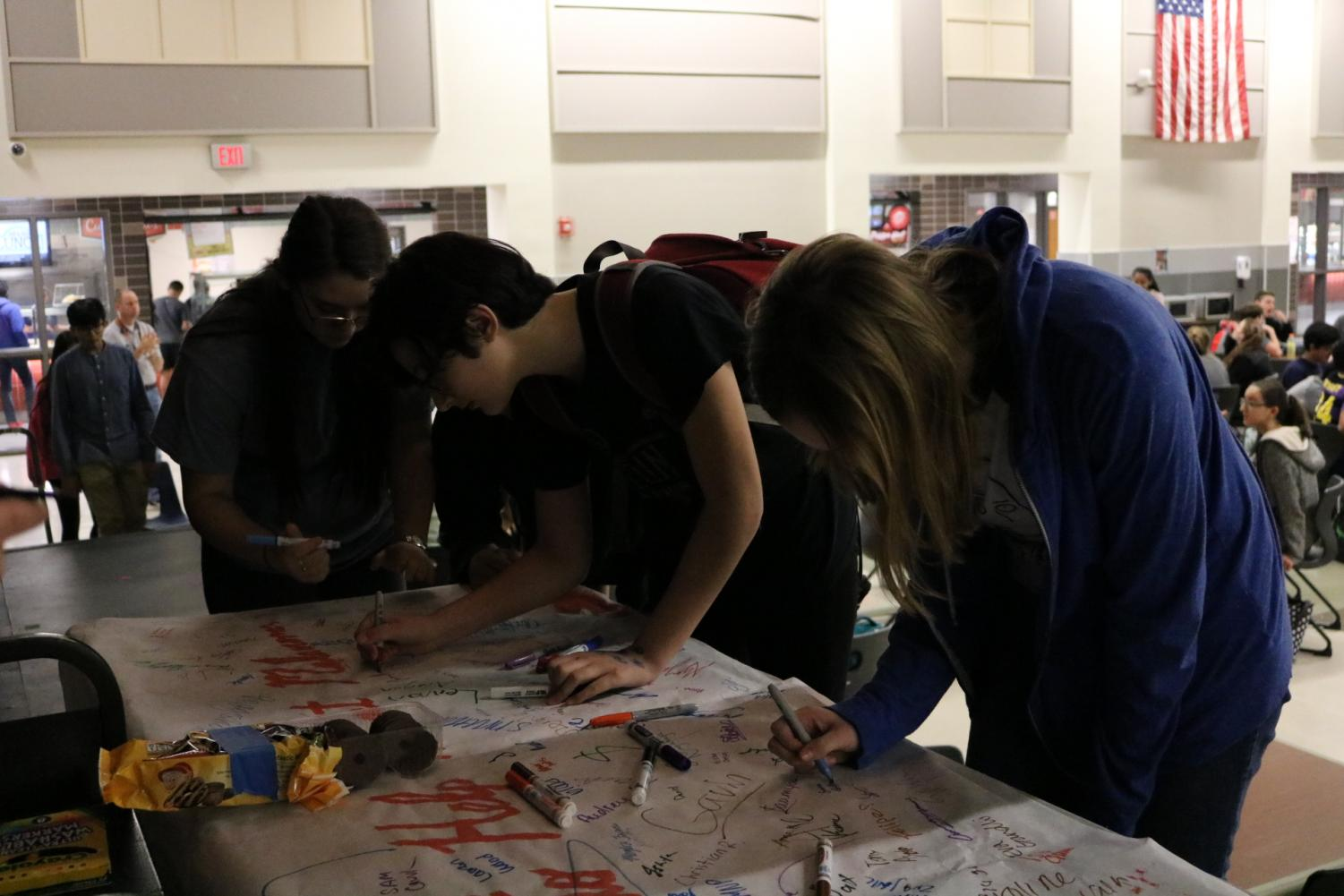 Westwood students sign a banner for Melanoma Awareness week.