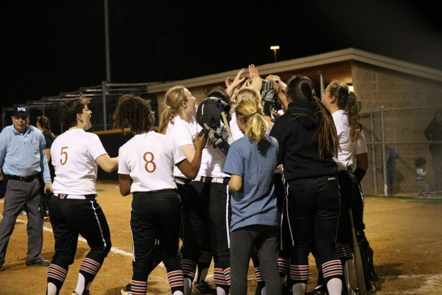 The team runs out on home base to celebrate senior Haley Popelka's home run.