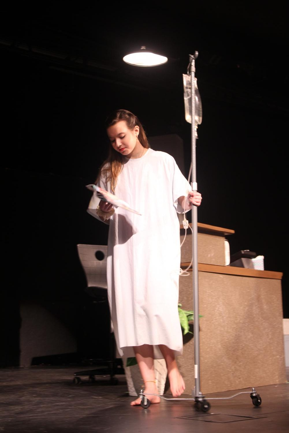Isabella Barber '19 walks across stage in a hospital gown.