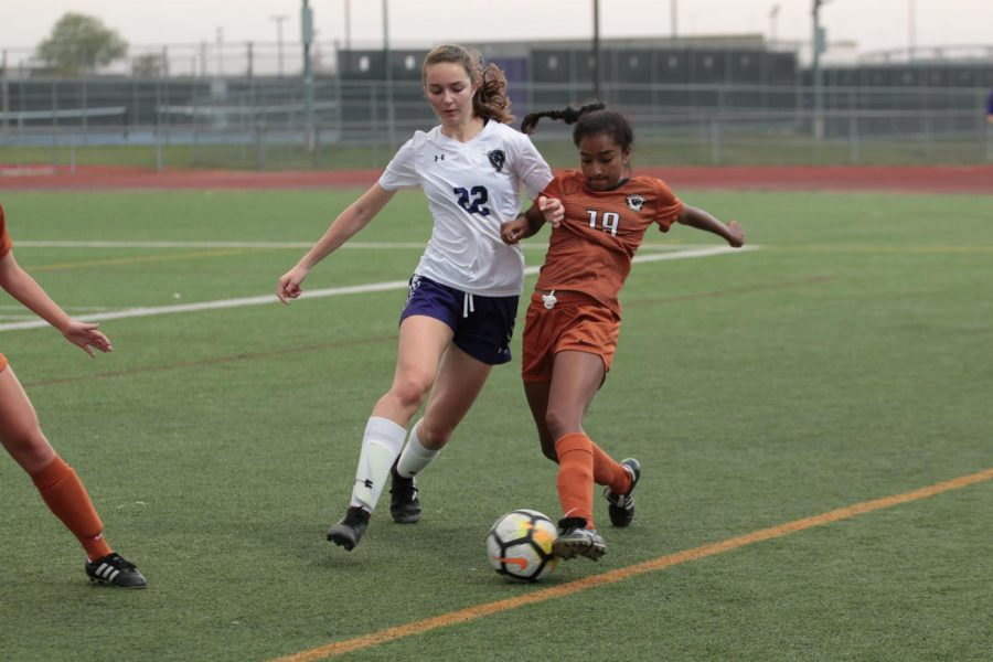 Deepti Choudhury '21 stops the ball from going out-of-bounds as a Raider defender pushes forward.