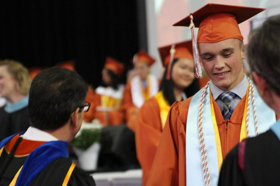 A senior walks off the stage after receiving his diploma.