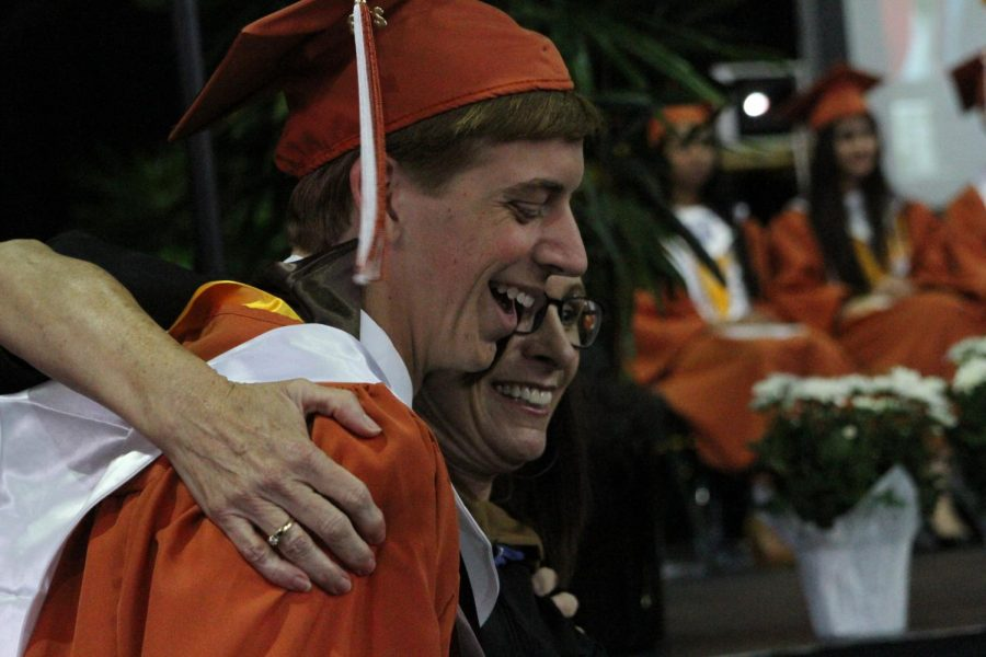 Senior hugs advisor before going on stage to receive his diploma