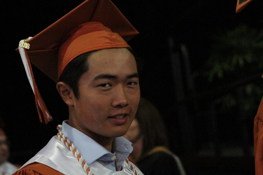 Student waits in line before receiving his diploma.