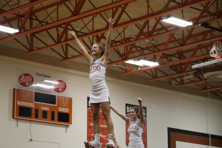 Claire Pitre 21 balances in the air during her cheer performance.