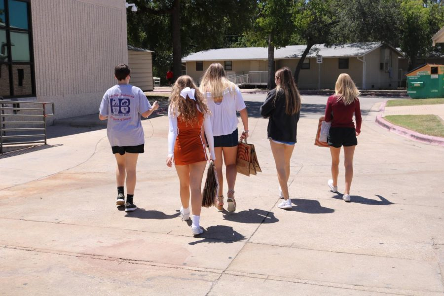 Students walk towards the portables to hand out their supply bags.