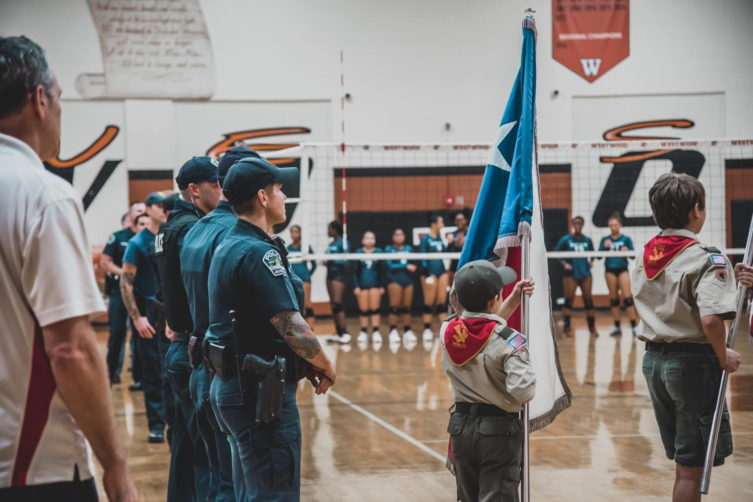The+police+officers+stand+as+they+boys+scout+troop+raises+their+flags+for+the+National+Anthem.+