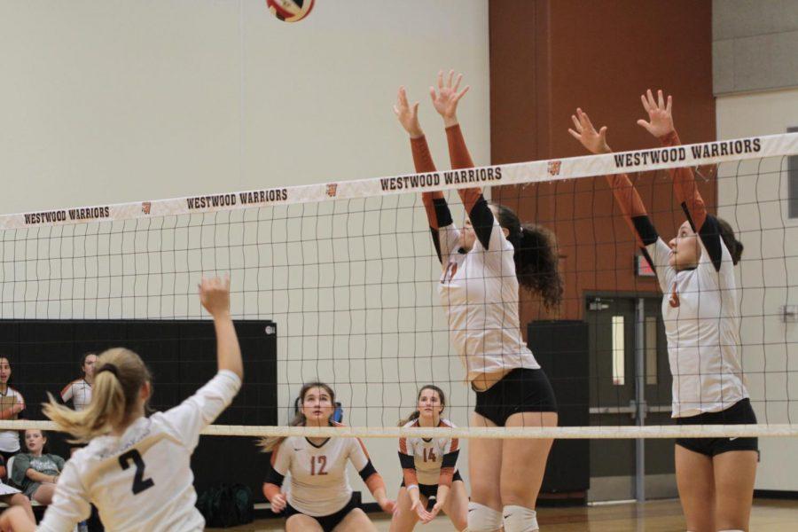 Bella Garcia 21 and Ellie Duff 22 jump to block the ball.