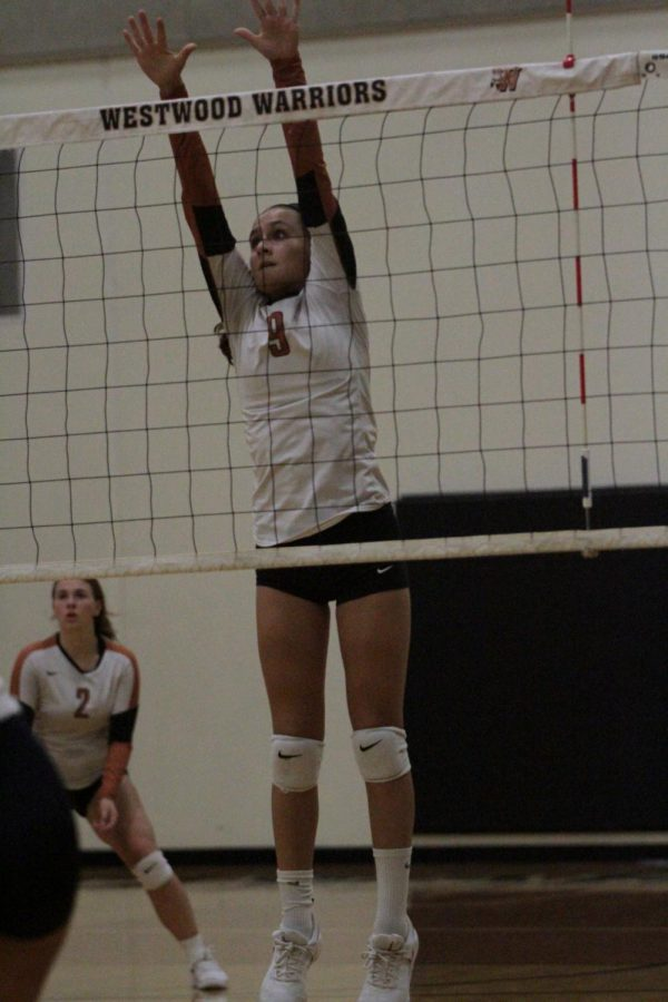 Ellie Duff 22 jumps to block the approaching ball.