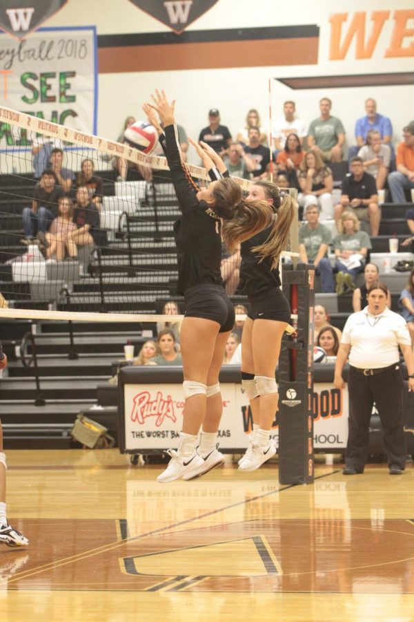 Abby Gregorczyk 21 and Kenzie Beckham 21 jump up to block the ball from entering their half of the court.