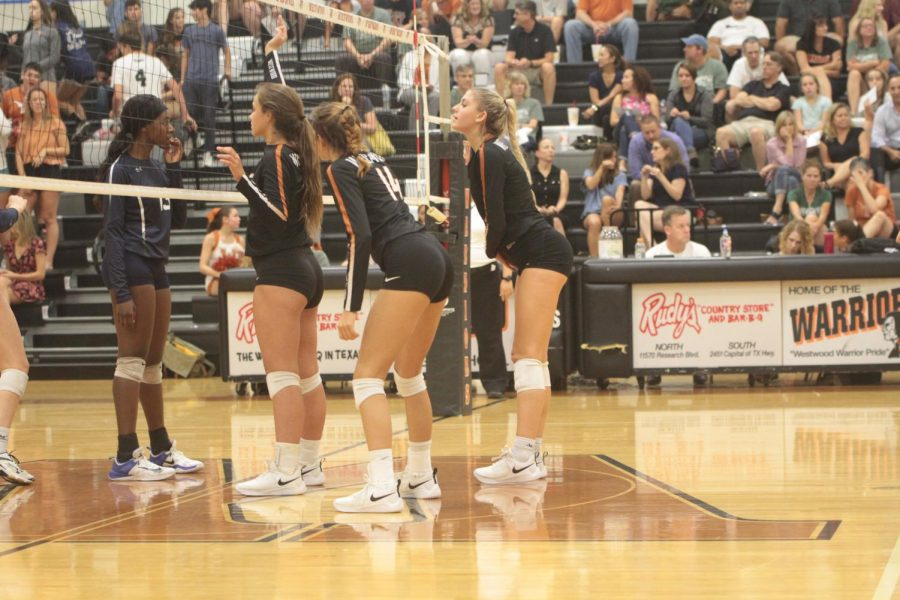 Abby Gregorczyk 21, Zoe Menendez 20, and Maggie Stout 19 prepare for the opposing team to serve the ball.