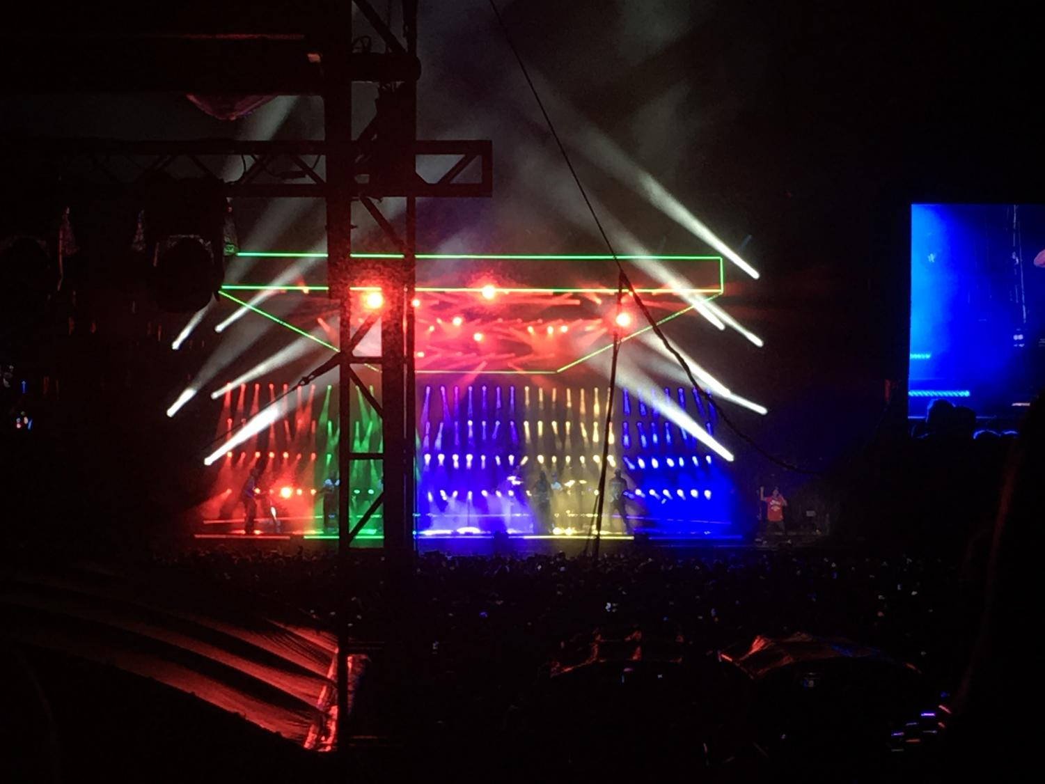 Bruno+Mars+sings+and+dances+to+his+opening+song+%22Finesse%22+with+colorful+lights+behind+him.