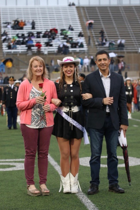 Homecoming+Court+Nominee+Ju+Ruiz+%2719+is+escorted+down+the+field+by+her+parents.