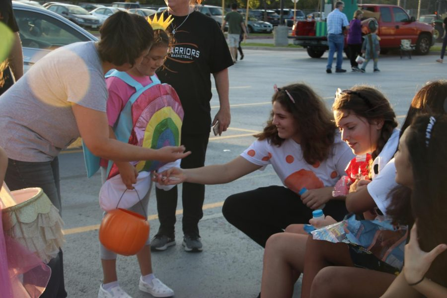 Emma Zion '21 gives candy to a trick-or-treater at the basketball trunk.