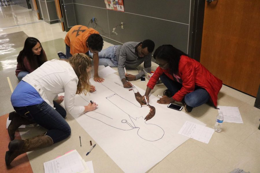 Students work together to add details to their poster.