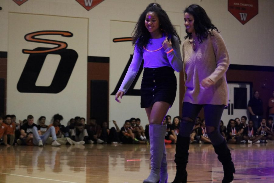 Members of the varsity girls' basketball team, seniors Makayla Coy and Oni Boodoo, walk back to the bleachers after talking about their game and upcoming season.