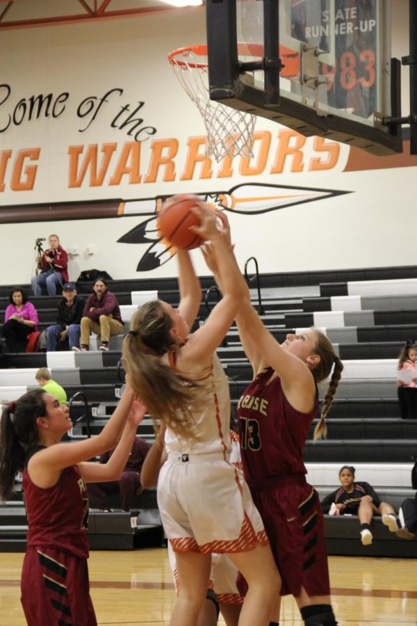 Kenzie Beckham 21 jumps to score a point, while defenders attempt to block the ball.