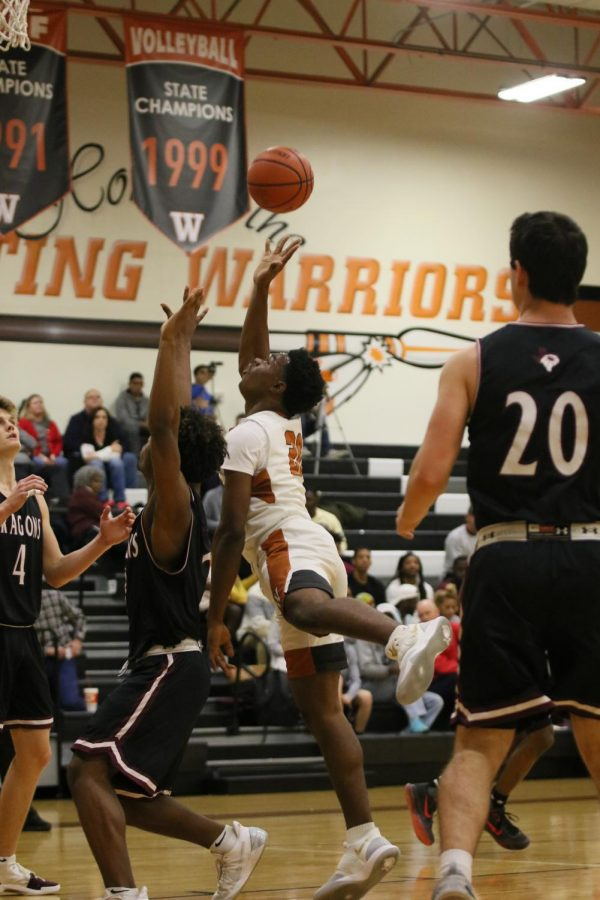 Brandon Parks '20 attempts to shoot over a defending Round Rock player in the Warriors game on Dec. 11.
