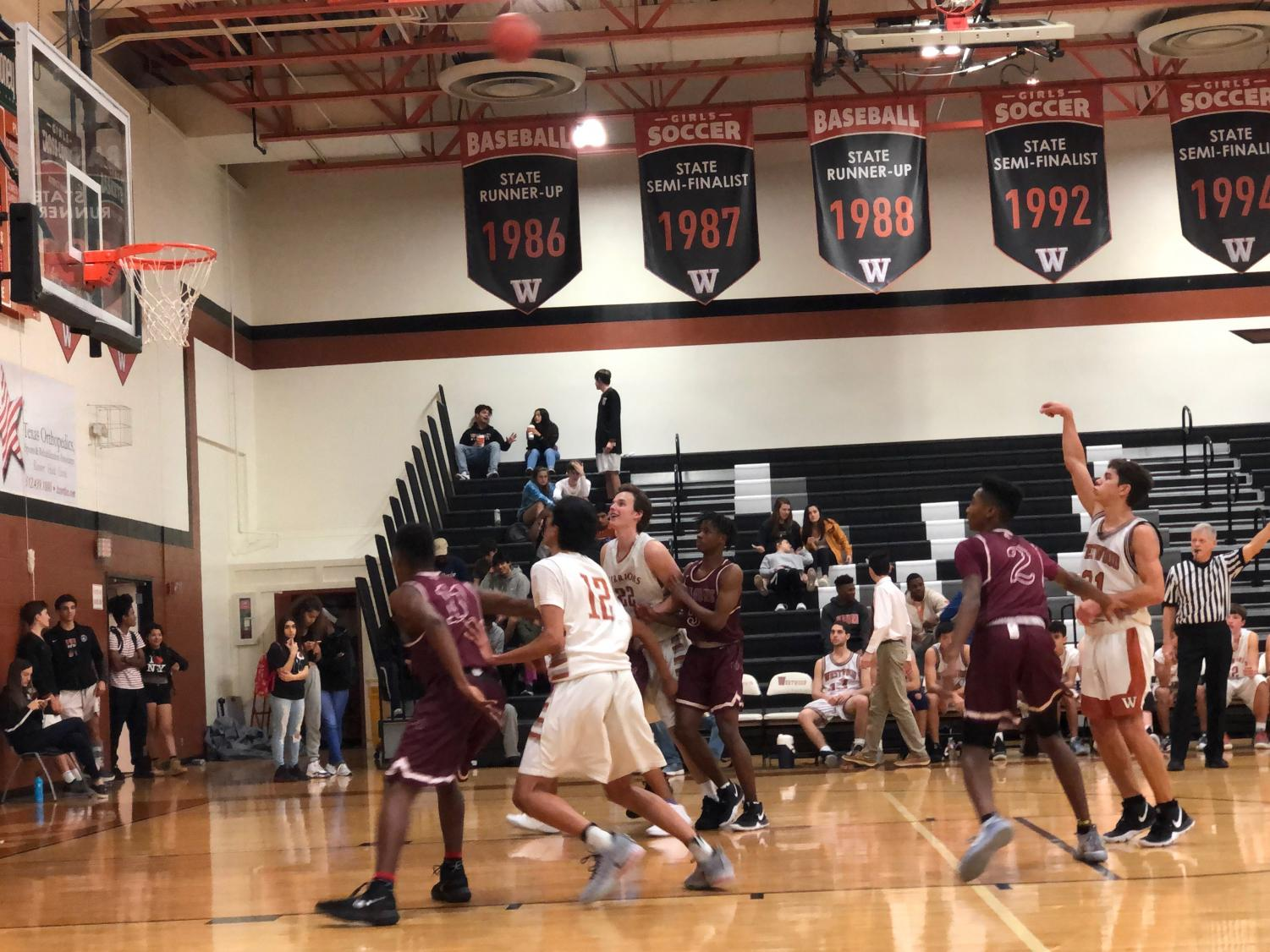 Lucian Tripon '21 shoots a high-arcing free throw to secure the win near the end of the game.