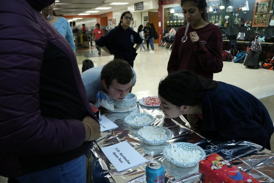 Students try to drop as many marshmallows as they can in a bowl with a spoon in their mouth.