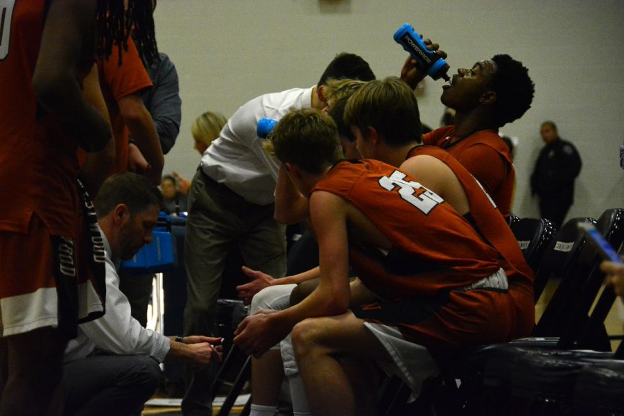 Coach Brad Hastings draws up a play for the Warriors during a timeout.