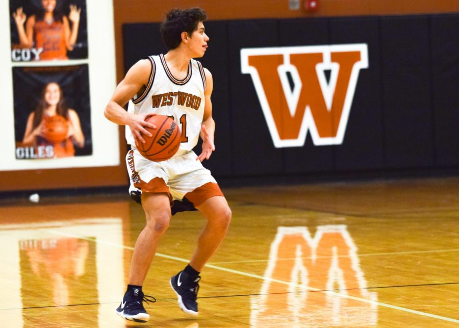 Looking for a teammate to make a pass, Luca Cipleu '21 dribbles the ball down the court.
