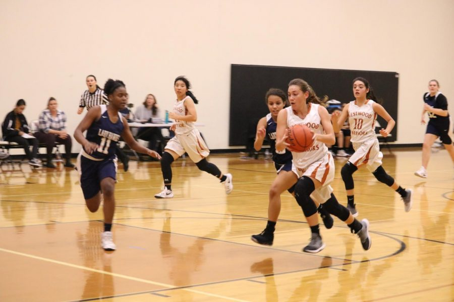 Gabbi Wallace '22 runs across the court while defending the ball.