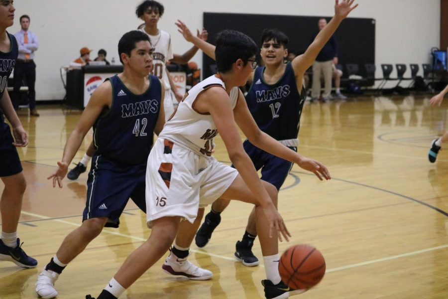 Eshaan Gulia '22 dribbles the ball as two opponents attempt to block him.