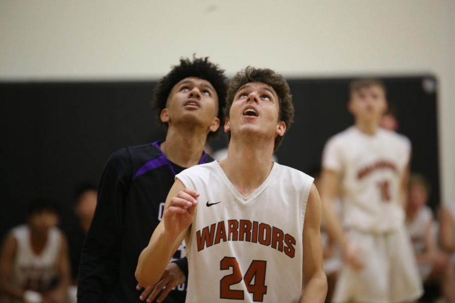 Ben Stankeys '22 and a Cedar Ridge player look up to see whether a teammate's shot was successful.