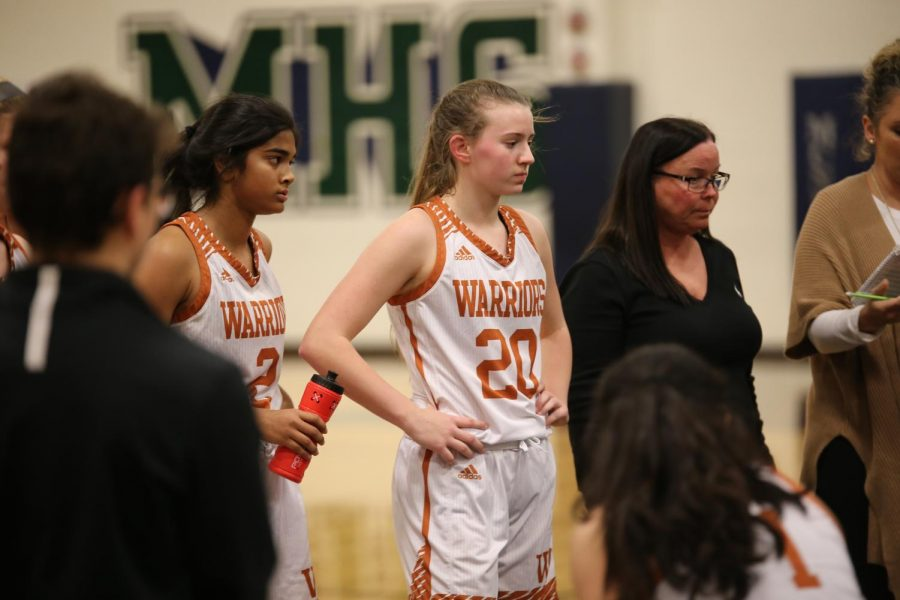 Sophomores Anisha Chintala and Kenzie Beckham listen in during a timeout.