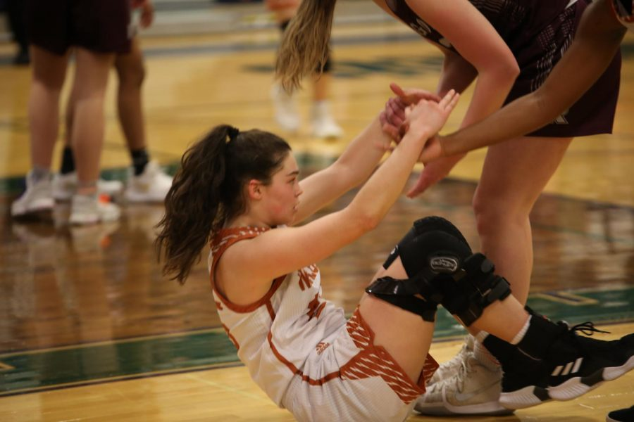 Makayla Coy '19 and a Round Rock player help Danielle Davalos '19 up after a fall.