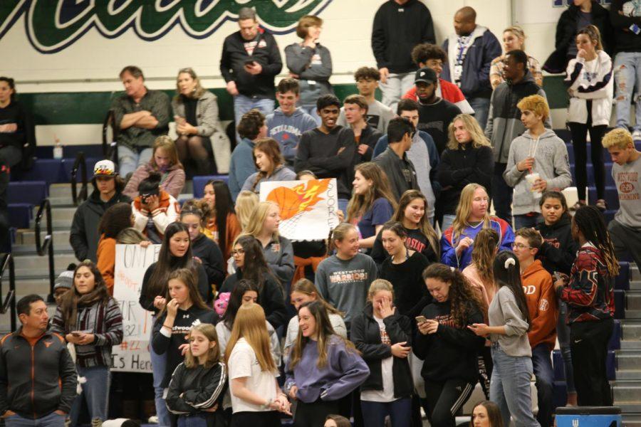 Several students, including Will Piejko '21, Demetrius Jones '19, Sarah Sherwood '20, and Emma Marsden '21, cheer the team on.