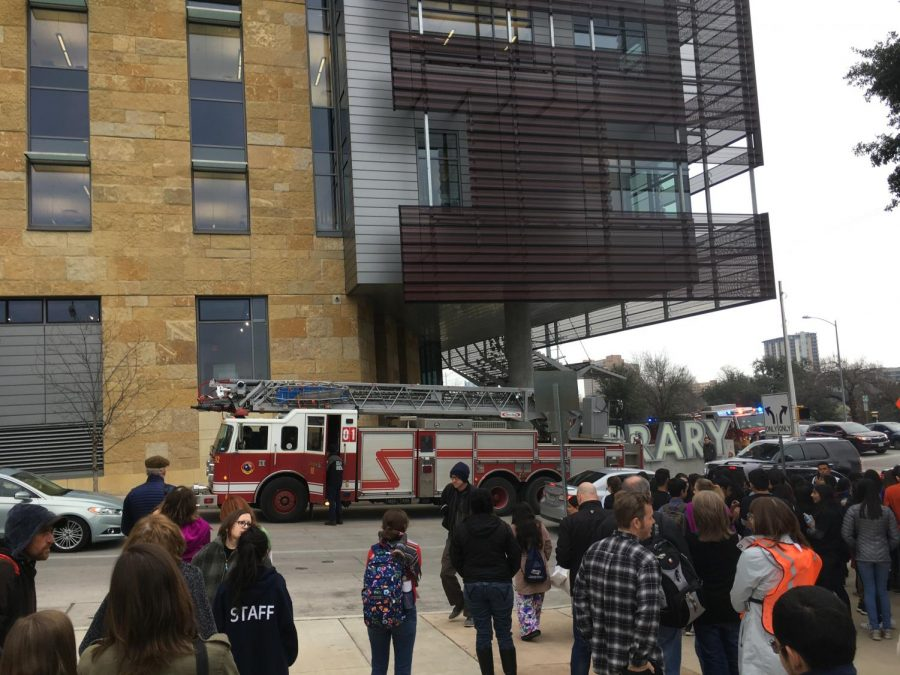 Students wait outside for instructions from the event coordinators while firetrucks line the side of the library.